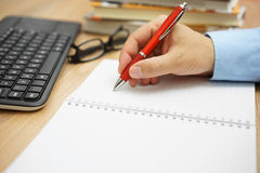 Office work, businessman hand is writes  in a notebook with book Royalty Free Stock Photos