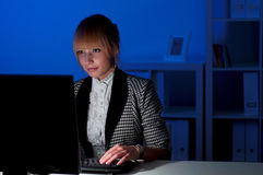 Office work at night. Beautiful young business woman working at night in the office Royalty Free Stock Image