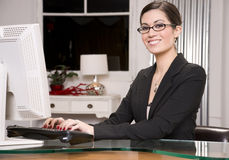 Office Worker Smiles While Entering Data Computer. A pretty receptionist smiles at the viewer Royalty Free Stock Photography