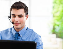 Office worker. Handsome man using an headset in front of a computer monitor Royalty Free Stock Image
