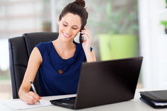 Office worker. Cute young office worker talking on cell phone in office Stock Photos
