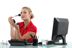 Office worker applying blusher Royalty Free Stock Image