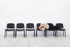 Office worker asleep on row of chairs Royalty Free Stock Image