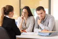 Office worker attending to a suspicious couple Royalty Free Stock Photo