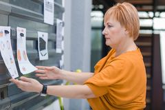 An office worker a woman examines working schedules on the wall. An office worker is a blond woman considering different working schedules that hang on the wall Stock Photo