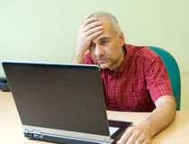 Office worker broken down. Office worker gone to pieces at the desk with laptop stock photos