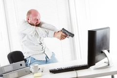 Angry Businessman Threatens Computer with a Gun Stock Photo