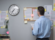 Office worker checking notes on pin board Royalty Free Stock Photography