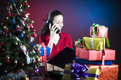 Office worker at Christmas. A view of an office worker talking on a telephone surrounded by Christmas presents and a Christmas tree Stock Photo