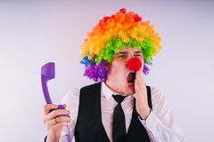 Office worker in clown wig, clown concept at work. Businessman with clown wig on white stock photos