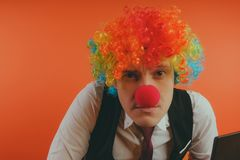 Office worker in clown wig, clown concept at work. stock image