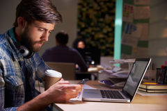 Office Worker With Coffee At Desk Working Late On Laptop Royalty Free Stock Photography