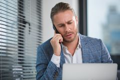 Office worker communicating on mobile phone. Waist up portrait serious bearded man sitting at work and talking on the cellphone. His face looking concentrated Stock Photos