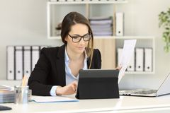 Office worker comparing report with tablet content. Office worker wearing eyeglasses comparing report with tablet content on a desk royalty free stock images
