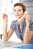 Office worker concentrating on phone call. Office worker woman concentrating on landline phone call with pen in hand, looking up smiling royalty free stock photos