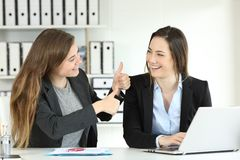 Office worker congratulating her colleague. For a good job stock photo