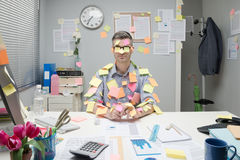 Office worker covered with stick notes. Office worker sitting at desk covered with colorful post it stick notes Stock Image