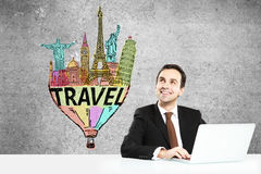 Office worker daydreaming about travel. Smiling businessman using laptop at office desk and daydreaming about vacation on concrete background. Travel concept Royalty Free Stock Photos
