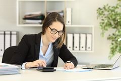 Office worker doing accounting on a desk. Office worker wearing eyeglasses doing accounting on a desk royalty free stock photos