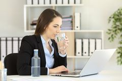 Office worker drinking water working on line Stock Image