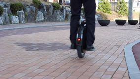 An office worker is driving on an electric mono wheel near the business center, back view stock video
