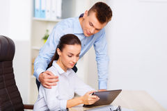 Office worker embraces his colleague from behind Stock Image
