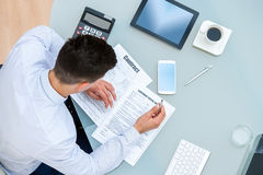 Office worker filling out contract documents. Royalty Free Stock Images