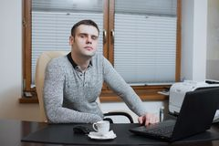Office worker freelancer sits at the desk and working on laptop during coffee break at the office Stock Photography