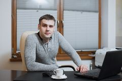 Office worker freelancer sits at the desk and working on laptop during coffee break at the office Royalty Free Stock Images