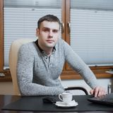 Office worker freelancer sits at the desk and working on laptop during coffee break at the office Stock Image