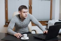 Office worker freelancer sits at the desk and working on laptop during coffee break at the office Stock Images