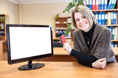 Office worker in front of a computer monitor with a credit card Royalty Free Stock Photography