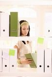 Office worker girl packing folders. Pretty office worker girl packing folders on shelf Royalty Free Stock Photography