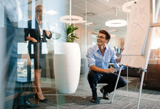Office worker giving a presentation to colleagues and smiling. Happy mature caucasian businessman near flip board with diagram. Office worker giving a stock photography