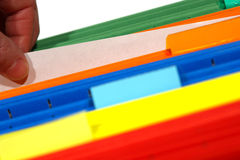 Office worker Hand Holding Paper in File Folders. Office worker hand holding and pulling out a blank sheet of paper from a stack of assorted colors file folders Royalty Free Stock Image