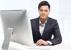 Office worker. Handsome man in business suit sitting at his desk in his office Royalty Free Stock Photo