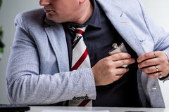 Office worker hiding a flask in internal pocket Royalty Free Stock Image