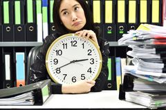 Office worker holding a clock, Working overtime and lot of work royalty free stock image