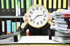 Office worker holding a clock, Working overtime and lot of work royalty free stock photos