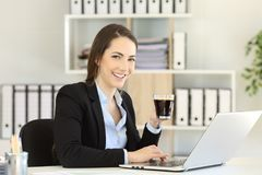 Office worker holding a coffee cup looking at camera. At workplace Stock Images