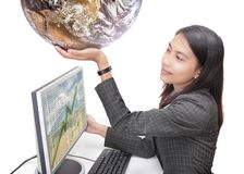 Office worker holding globe. Happy young Asian businesswoman in corporate outfit sitting at her desk in front of her computer screen with spreadsheet data and Stock Photos