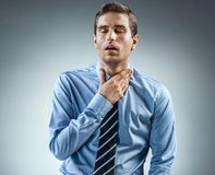 Office worker holding his inflamed throat. Throat Pain. Office worker holding his inflamed throat. Photo of man in blue shirt and tie on gray background Royalty Free Stock Images