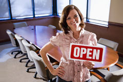 Office worker holding open sign in empty boardroom Stock Photo