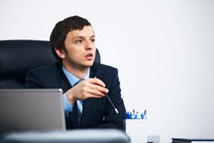 Office worker holding pencil thinking in office. Stock Photography