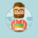 Office worker holding pile of folders. Young smiling hipster office worker standing with pile of folders in the office. Happy employee working in office with Stock Photography