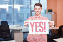 Office worker holding poster with yes slogan Stock Photo