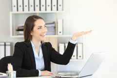 Office worker holding something blank. Over a white  wall Royalty Free Stock Photos