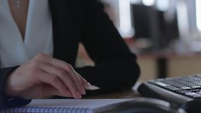 Office worker holds pencil while working with notebook and computer sitting at desk in office stock footage
