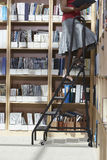Office Worker On Ladder In File Storage Room Stock Images