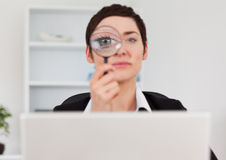 Office worker looking through  a magnifying glass Stock Photos